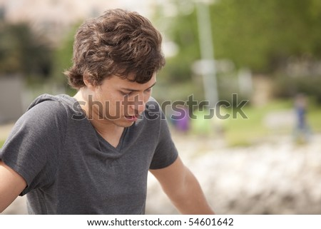 sad teenager looking down in outdoor - stock photo