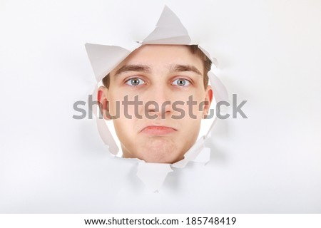 Sad Teenager peeking through Paper Hole - stock photo