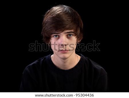 Sad teenager portrait isolated on black background - stock photo