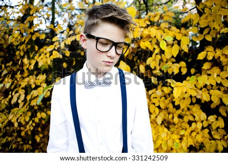 Sad teenager posing in autumn atmosphere. Dressed in suspenders and bowtie