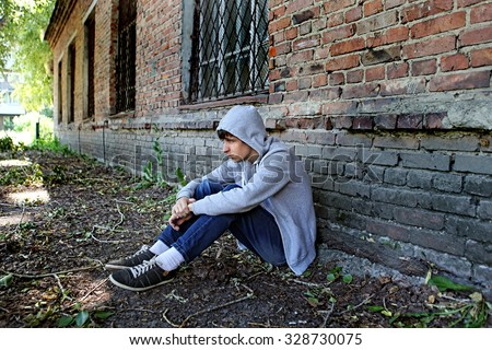 Sad Teenager sit on the Brick Building Background - stock photo
