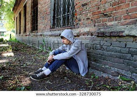 Sad Teenager sit on the Brick Building Background - stock photo