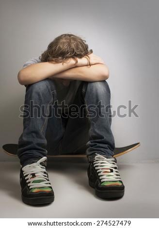 sad teenager sitting on skateboard - stock photo