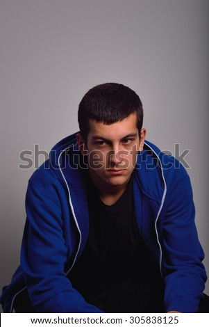 Sad teenager with blue sweatshirt standing against a dirty wall - stock photo