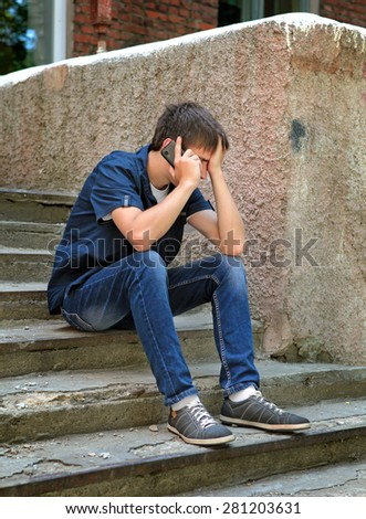 Sad Teenager with Cellphone on the Landing Steps of the Old House - stock photo
