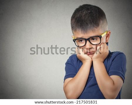 Sad, thinking. Closeup portrait headshot depressed, alone, tired child resting head on fist  isolated grey wall background. Negative human emotion face expression feeling life perception body language - stock photo
