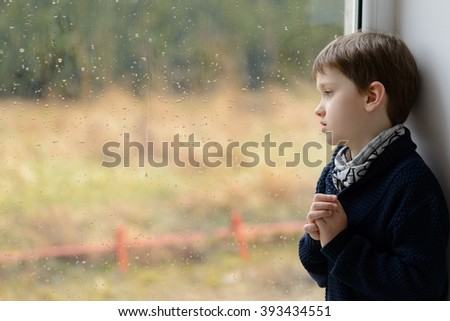 Sad thoughtful little boy looking through the window. Copy space for text on glass. Rainy day