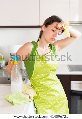 Sad tired housewife cleaning furniture in kitchen