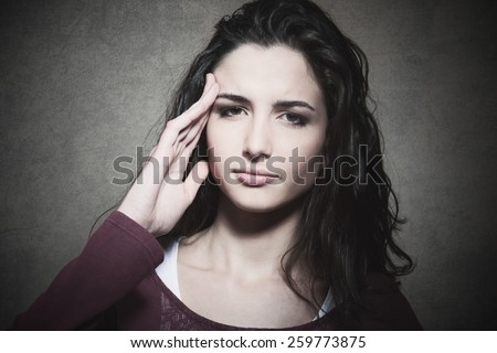Sad tired young woman with headache touching her temples - stock photo