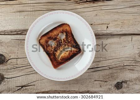 Sad toast on an old wooden board - stock photo