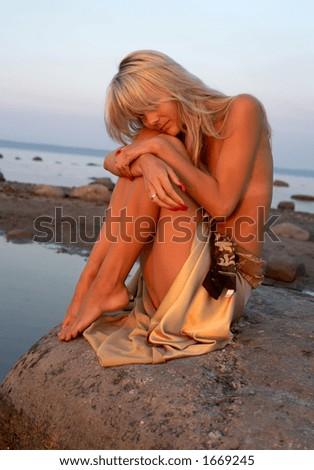 sad topless girl on the rock - stock photo