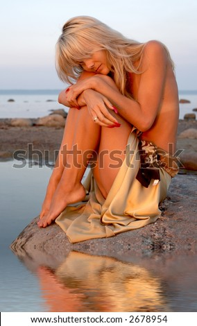 sad topless girl sitting on the rock with water reflection - stock photo