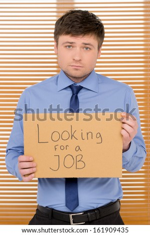 Sad unemployed man is looking for a job. Showing plate with sign  - stock photo