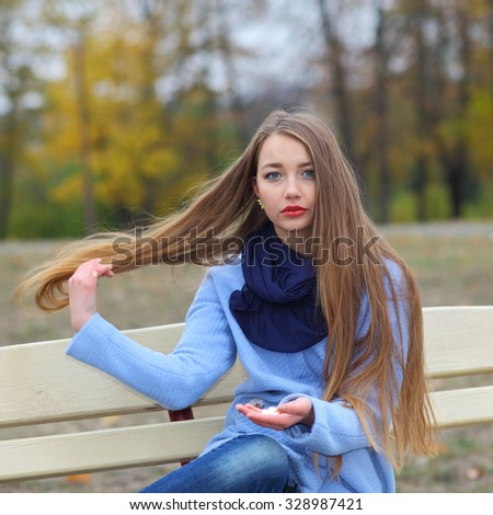 sad unhappy girl with pills outdoors in autumn - stock photo