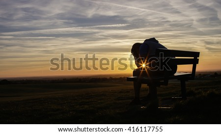 Sad unhappy silhouette man sitting with his head in his hands on a bench at sunset - stock photo