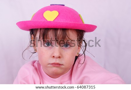 Sad, uninterested girl with a happy pink hat - stock photo
