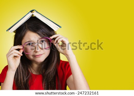 Sad, upset, overworked Portrait of a cute little schoolgirl  with a open book on her head, isolated over yellow background. - stock photo