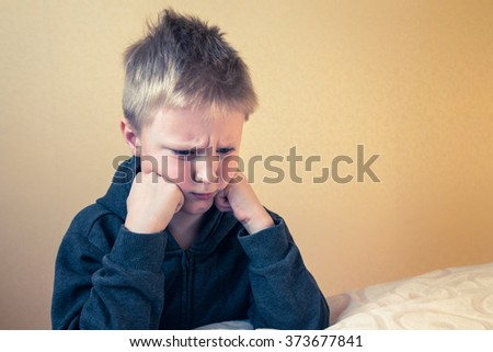 Sad upset tired worried unhappy kid (boy, teen) close up portrait with copy space - stock photo