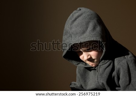 Sad upset tired worried unhappy little child (boy) close up horizontal dark portrait with copy space - stock photo