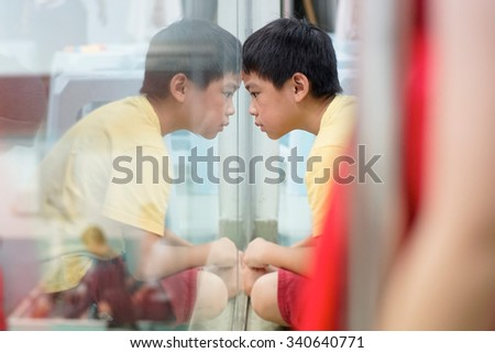 Sad upset waiting boring depressed child (boy) near a window, reflection. - stock photo