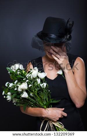 sad widow crying at husband's funeral - stock photo