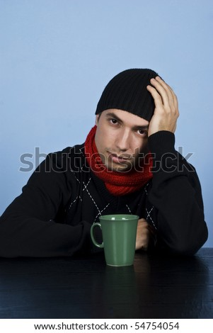 Sad winter man sitting at table with a hot drink and  being depressed and holding his hand on head over blue background - stock photo
