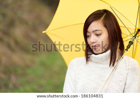 Sad wistful young Asian woman walking along outdoors under a yellow umbrella staring disconsolately at the ground - stock photo