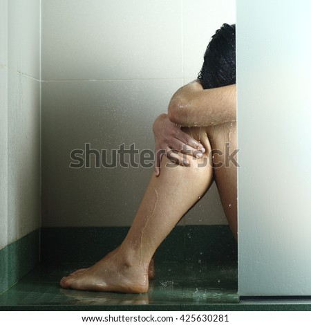 Sad woman after abuse crying under the water in the shower - stock photo