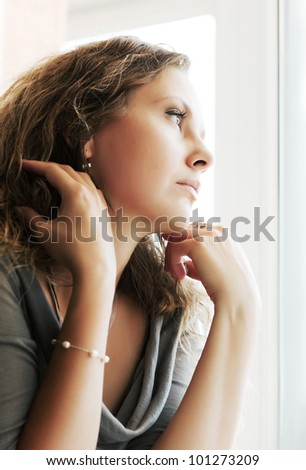 Sad woman against a window - stock photo