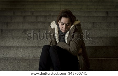 sad woman alone on street subway staircase suffering depression looking looking sick and helpless sitting lonely as female victim of abuse concept  in  dark urban night grunge background