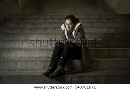 sad woman alone on street subway staircase suffering depression looking looking sick and helpless sitting lonely as female victim of abuse concept  in  dark urban night grunge background  - stock photo
