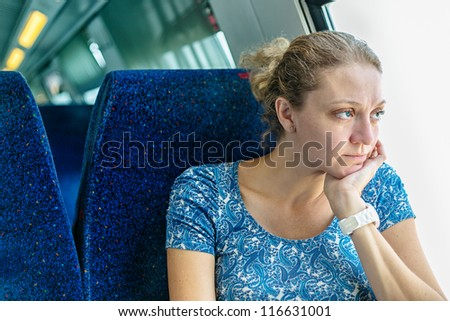 sad woman at the window of a train - stock photo
