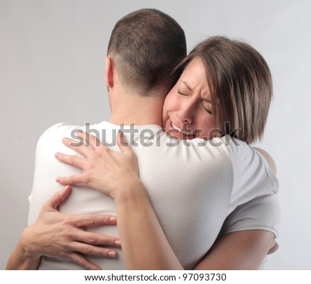 Sad woman crying on her husband's shoulder