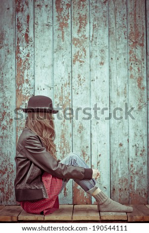 Sad woman deep in thought sitting over grunge wooden background. toned vintage image - stock photo