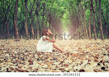 Sad woman hands off her face so sadly sitting on dry leaf in the forest - stock photo