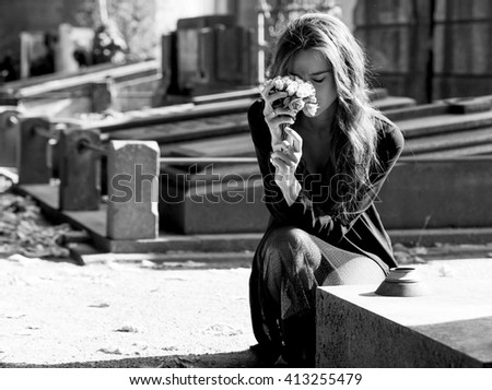 Sad woman holding bunch of flowers near a grave monochrome - stock photo