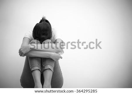 sad woman hug her knee and cry (monochrome) - stock photo