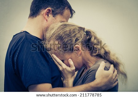 Sad woman hugging her husband - stock photo
