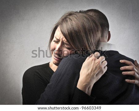 Sad woman hugging her husband - stock photo