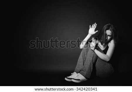 sad woman in depression and despair crying on black dark background - stock photo