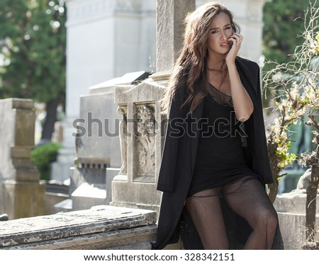 Sad woman in grief sitting near a grave - stock photo