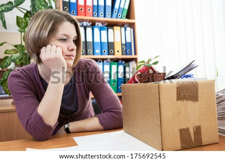 Sad woman in the workplace after dismissal - stock photo