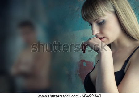 Sad woman indoors and defocused man as a symbol of relationship crisis - stock photo