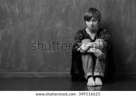 Sad woman is sitting against the wall, reproachful look. Black and white - stock photo