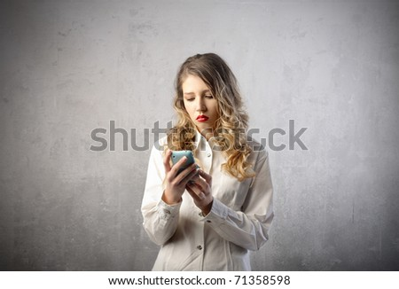 Sad woman looking at her mobile phone - stock photo