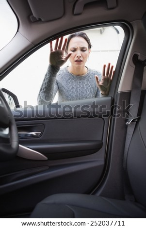 Sad woman looking inside the car - stock photo