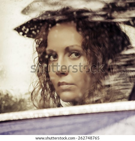 Sad woman looking out car window - stock photo