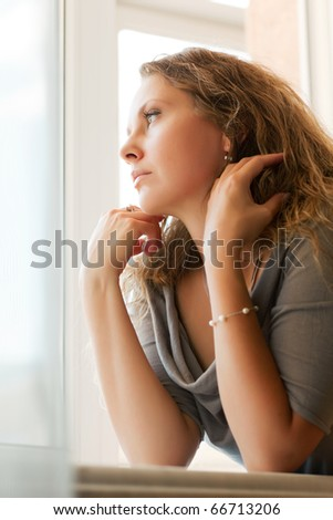 Sad woman looking out the window. - stock photo