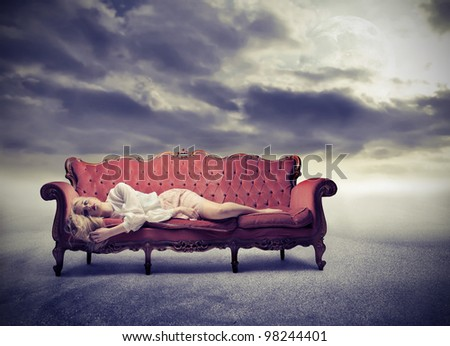 Sad woman lying on a sofa - stock photo