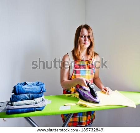 sad woman of doing the ironing. Housework - stock photo